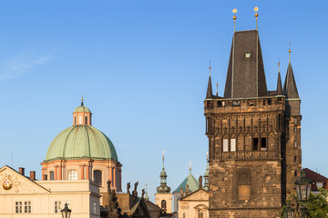 St. Francis of Assissi Church's dome and Old Town Bridge Tower at the Old Town in Prague, Czech Republic, on a sunny day.