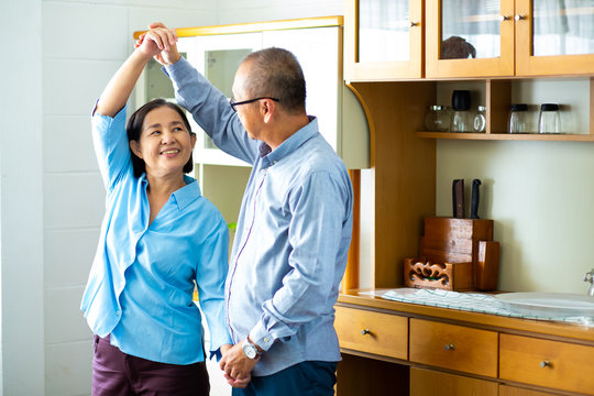 Asian senior couple is dancing and smiling while cooking together in kitchen
