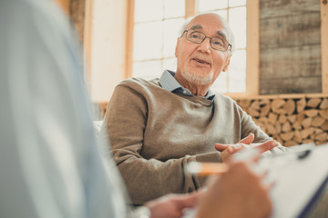 Bald senior in cozy sweater talking with his doctor