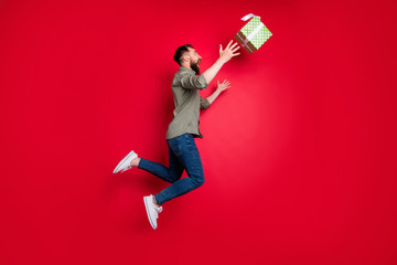 Full length body size photo of man trying to catch his prize gift while isolated with red background
