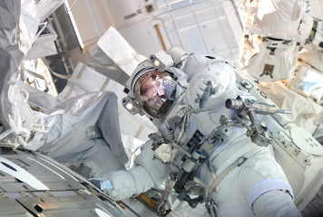 The astronaut in a space suit, in the ISS, lasts a hand in the camera.  Elements of this image were furnished by NASA