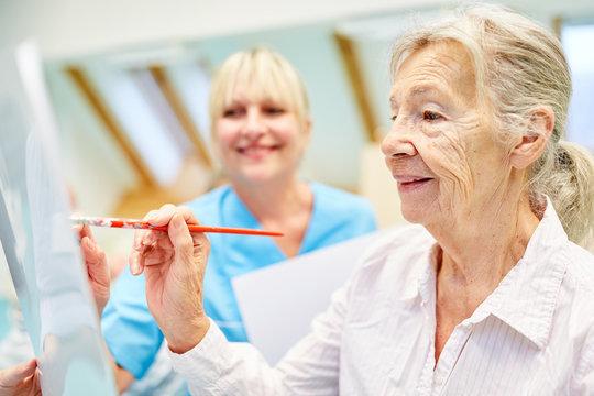 Senior Frau im Malkurs in einer Maltherapie
