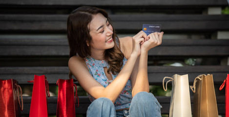 Happy young Asian woman with credit card and shopping bags buy things at shopping mall.