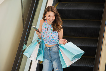 Happy time to shopping concept , Asian woman holding shopping bags and smartphone in hands on escalator at mall centre.