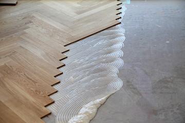 Obraz Worker laying parquet flooring. Worker installing wooden laminate flooring - fototapety do salonu