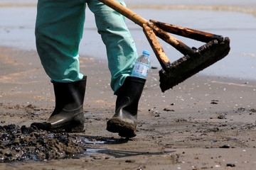 A worker scrapes sand as he cleans a beach affected by oil spill at a shoreline in Karawang