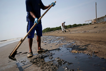 Workers scrape sand affected by oil spill at a shoreline in Karawang