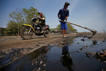 A worker scrapes sand affected by oil spill as he cleans a beach at a shoreline in Karawang