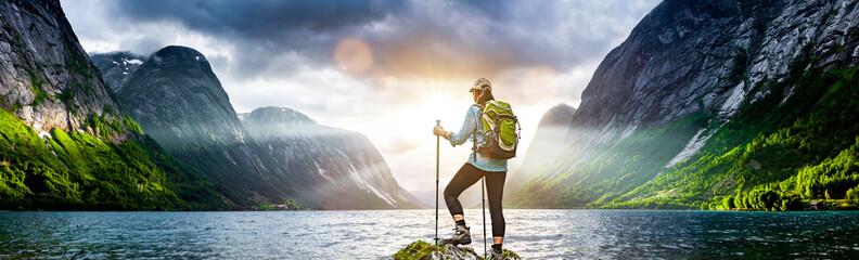 Frau mit Rucksack beim Wandern an einem Fjord in Norwegen Wall mural