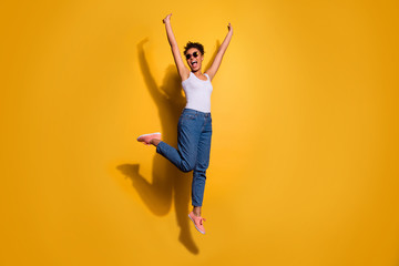 Full length body size photo beautiful she her dark skin excited lady jumping high yell yeah yes triumphant champion wear casual jeans denim pants trousers tank-top isolated bright yellow background