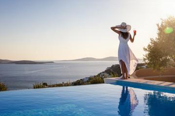 Frau mit weißem Hut steht am Pool und genießt die Aussicht auf das Meer bei Sonnenuntergang mit einem Aperitif in der Hand