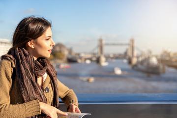 Atraktive Touristin mit Stadtplan in der Hand steht vor der Tower Bridge in London bei Sonnenuntergang