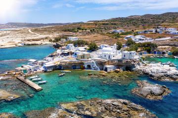 Luftaufnahme des traditionellen Fischerdorfes Mandrakia auf der Insel Milos, Griechenland, mit den bunten Bootshäusern direkt am Wasser