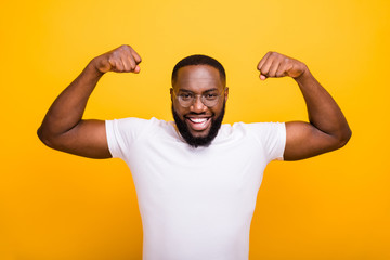 Close up photo of dark skin guy showing big biceps wear casual outfit isolated yellow background Wall mural