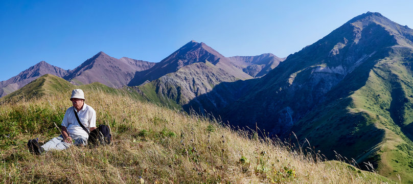 A panorama of a mountain valley from a bird's flight. Adult man looks into the distance. nature, mountains, lit by the sun in clear weather, sunset, summer dawn in the mountains. Traveling, hiking.