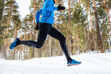 Fototapete - legs athlete runner run through the winter forest training.