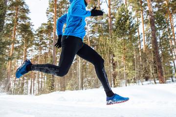 Wall Mural - legs athlete runner run through the winter forest training.