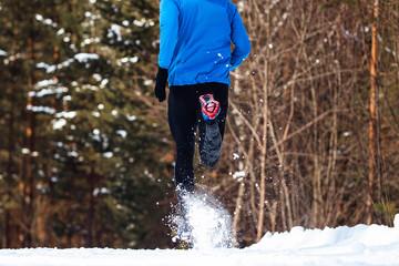 Wall Mural - back athlete runner run in winter forest snow spray from under feet.