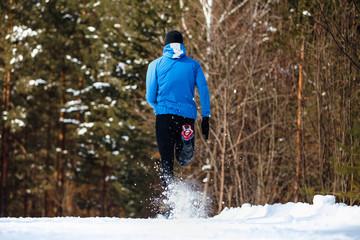 Wall Mural - back athlete runner running in winter trail snow spray from under legs