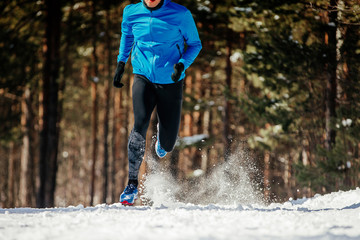 Fototapete - dynamic running on winter trail athlete runner in blue jacket