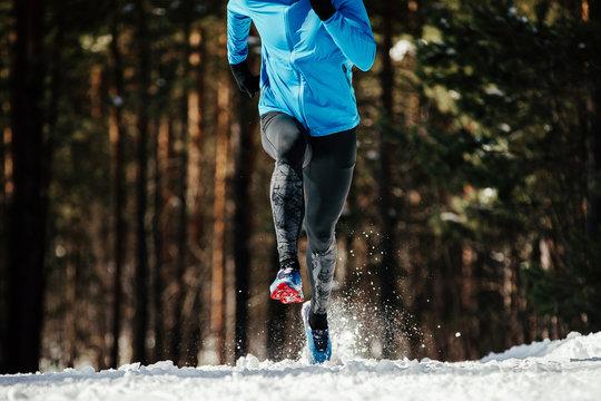 athlete runner running in winter trail snow spray from under legs