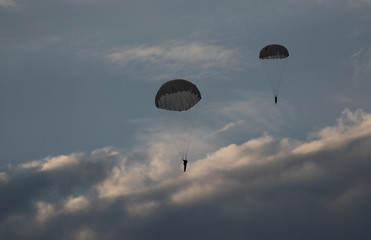Belarusian paratroopers from special forces are seen in the sky during the International Army Games 2019 at a shooting range near the village of Mukhovets