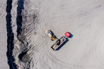 Aerial view of sand quarry with trucks and bulldozers. Heavy bulldozer loading  sand,