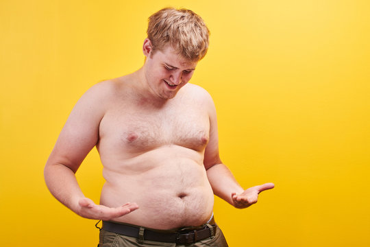 Huge funny young man with naked body touches big fat belly on yellow background in studio. Concept of obesity, fast and junk food, sports, liposuction, weight loss