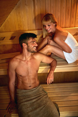 Couple detoxing body in sauna