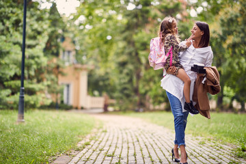 smiling mother holding a daughter with schoolbag