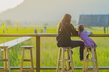 Mom and daughter sit for resting and waiting for time to take photos of the sunset on the farmer's balcony in the rice fields.