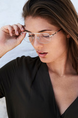 Beautiful woman adjusting spectacles, looking down
