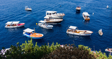 Boats with tourists waiting to enter the blue cave in the south of Capri island (Italy). Idyllic blue sea a sunny summer day with green vegetation in the foreground. – Image