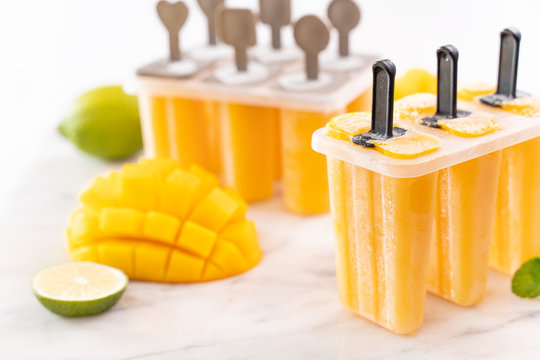 Fresh mango fruit popsicle ice in the plastic shaping box on bright marble table. Summer mood concept product design, close up.