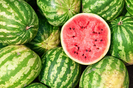 Red ripe watermelon cut in half on a pile of ripe watermelons in the field. A red cut watermelon view from above.
