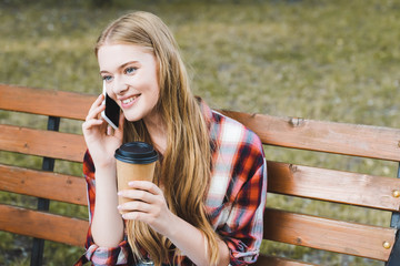 Wall Mural - beautiful girl in casual clothes holding paper coffee cup while sitting on wooden bench in park and talking on smartphone