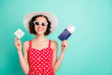 Pretty lady holding registration documents on low cost airline trip having fun wear red dress isolated teal background