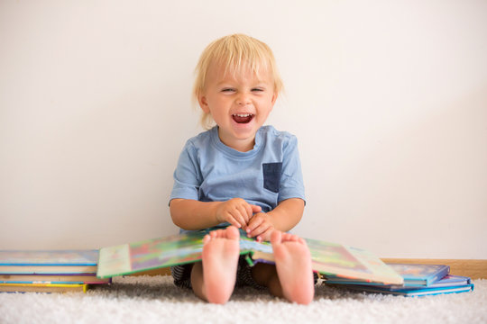 Sweet toddler boy, reading book at home, sitting on the ground, lots of books