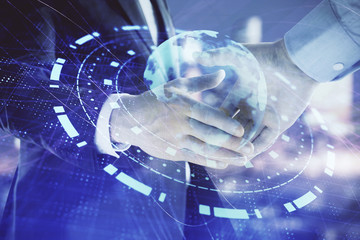 Double exposure of world map on cityscape background with two businessmen handshake. Concept of...