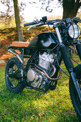 Closeup of beautiful vintage custom motorcycle parked on the field