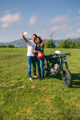 Young couple taking a selfie with a motorcycle outdoors