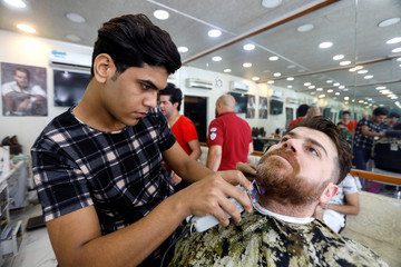 A barber shaves a cutomer's beard at his shop in preparation for Eid Al-Adha celebration in Baghdad