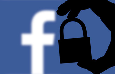 LONDON, UK - FEBRUARY 5th 2018: Facebook security issues. Silhouette of a hand holding a padlock infront of the facebook logo