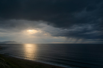 dark seascape with stormy clouds and rain at sunset