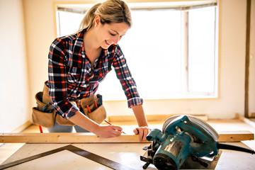 Fototapeta A woman worker in the carpenter workroom renovation obraz