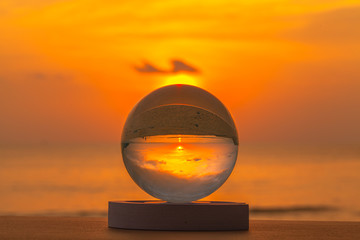 crystal glass ball sphere reveals sunrise seascape with spherical perspective on the beach in Phuket island
