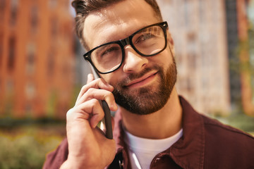 Wall Mural - Sharing great news. Close up portrait of happy bearded man in casual wear and eyeglasses talking by phone and smiling while standing on the street