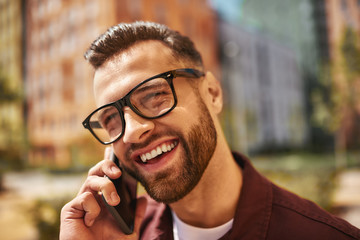 Wall Mural - Sunny day. Handsome young bearded man in casual wear walking through the city street and smiling