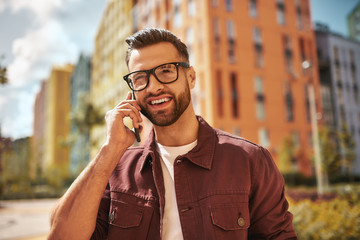 Wall Mural - Happy to hear you Portrait of cheerful and handsome bearded man in casual wear and eyeglasses talking by phone and smiling while standing on the street