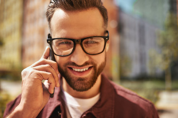 Wall Mural - Always in touch. Portrait of cheerful and handsome bearded man in eyeglasses talking by phone and smiling while standing on the street